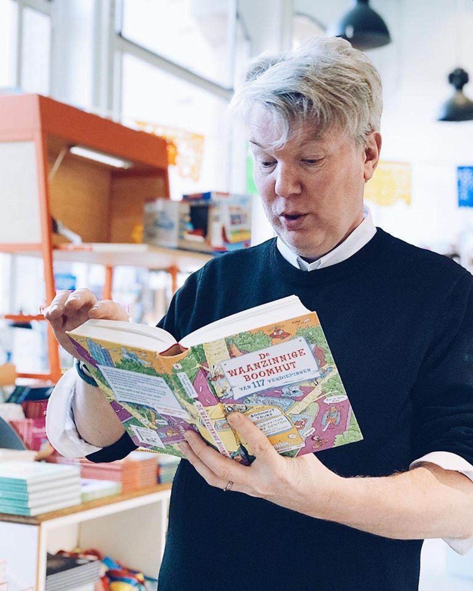 Daniel Albering leest een boek in de winkel